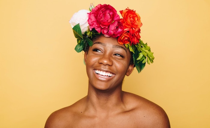 Beautiful woman with flower crown on a yellow backround