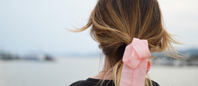 Close up of womans head with ribbon in hair