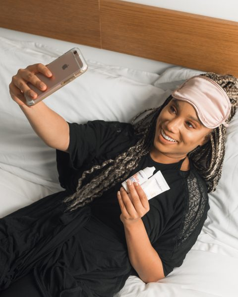 Woman taking selfie wearing eye mask and holding products