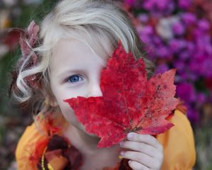 Young girl holding up red autumn leaf