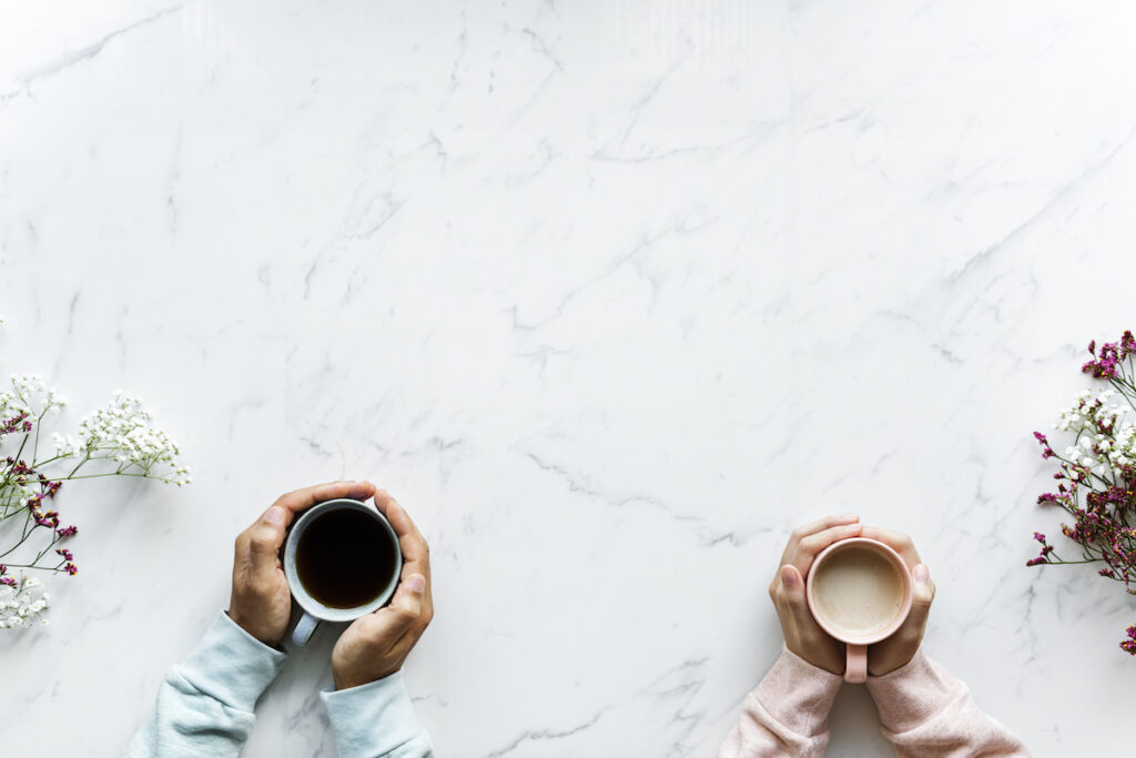 Two people holding coffee cups