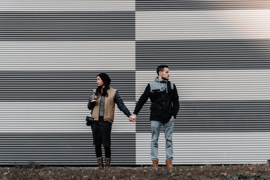 Couple holding hands but facing apart