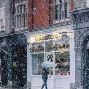 A person walks through the snow shopping for gifts