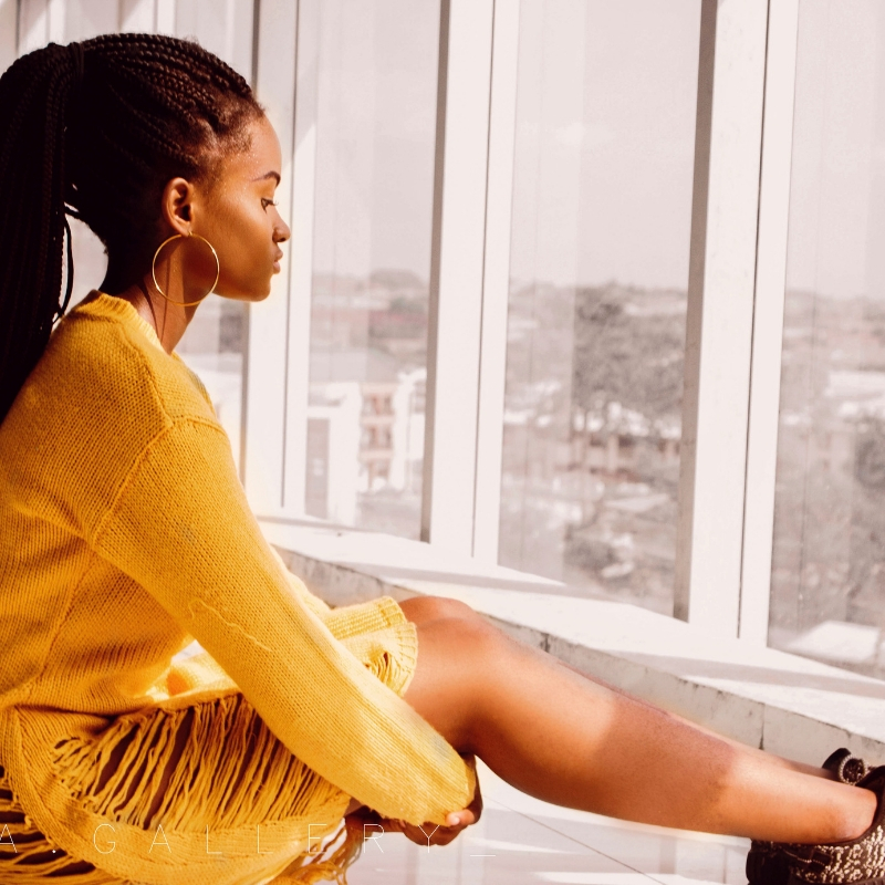 A young woman sits with her hands clapsed around her legs, looking out of the window.