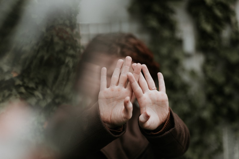Woman with hands in front of her face