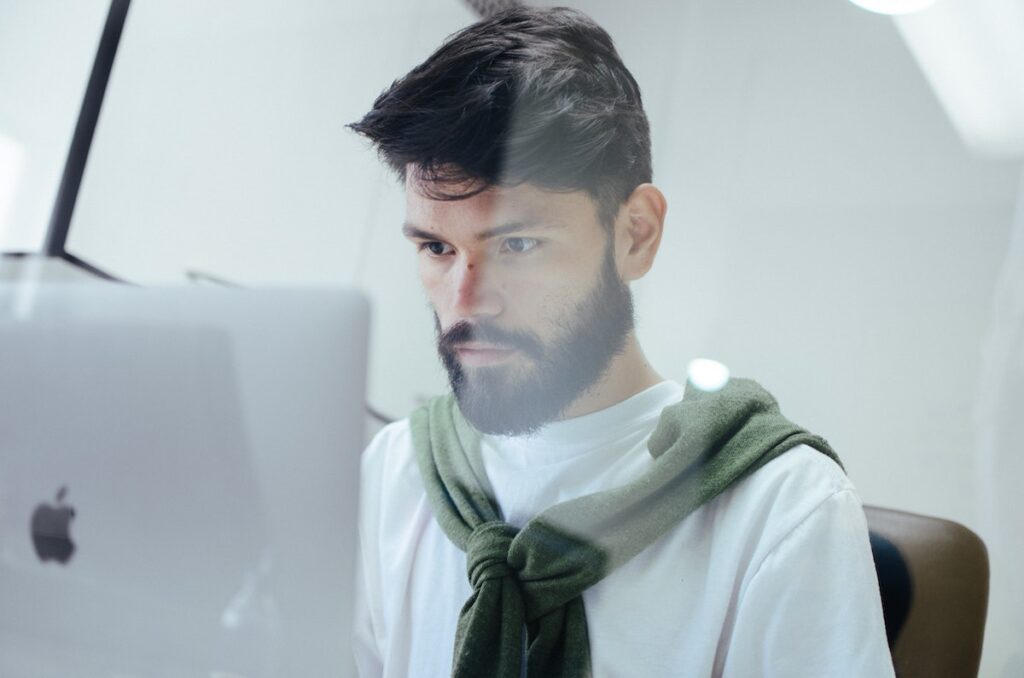 Image of a man with dark hair sitting at a laptop