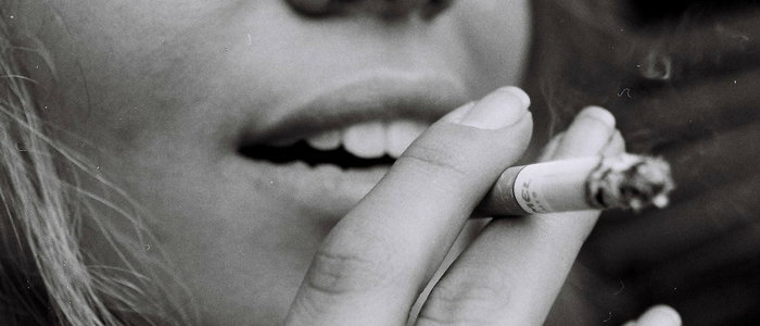 woman holding cigarette to mouth