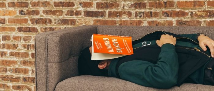 Man sleeping on sofa with book over face