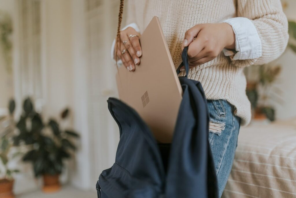 Image of a woman packing away a laptop into her bag