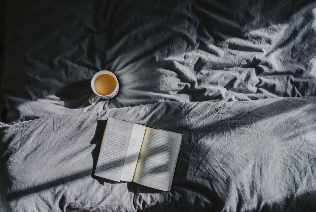 Image of a book and mug of tea on bedding