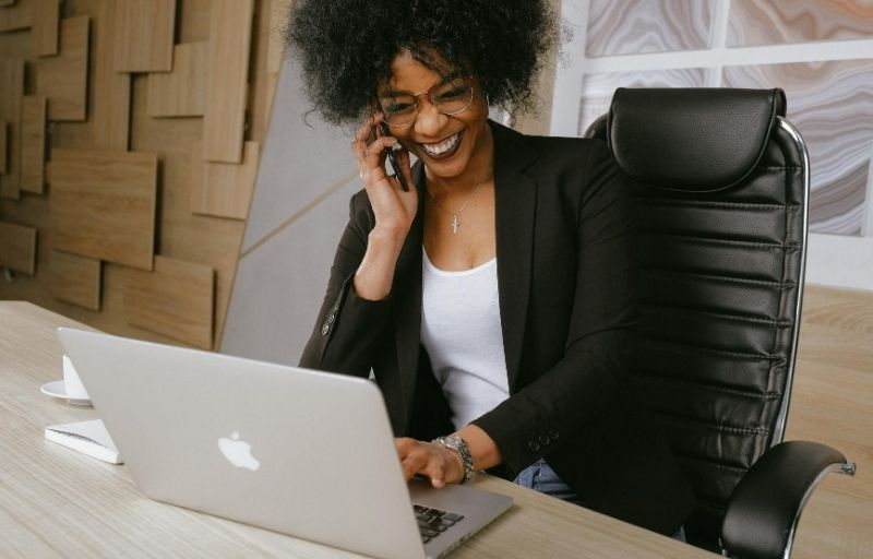 Image of a woman working at a laptop while laughing on the phone