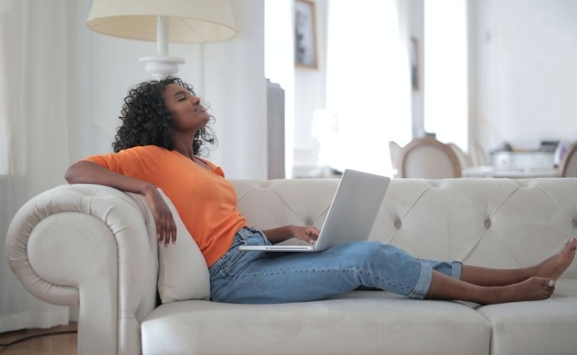 Woman working on sofa with eyes closed