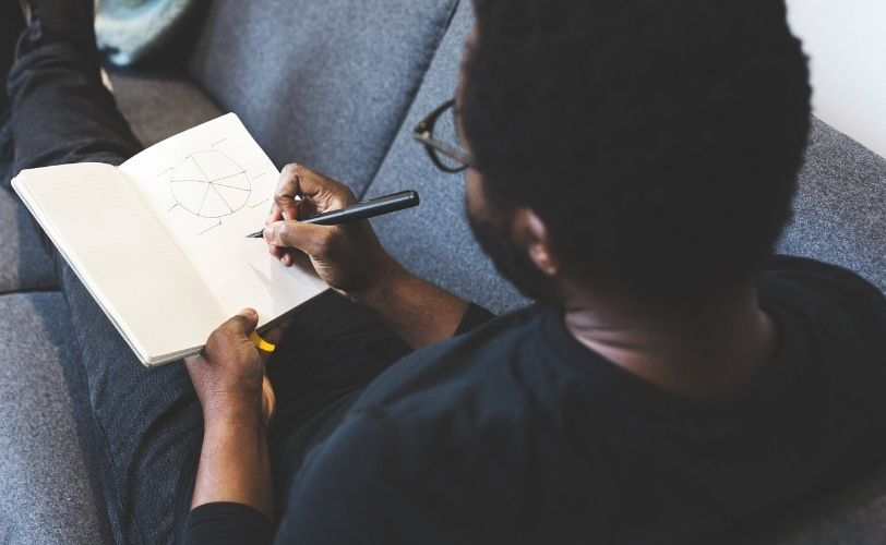 Man journaling about his creative business