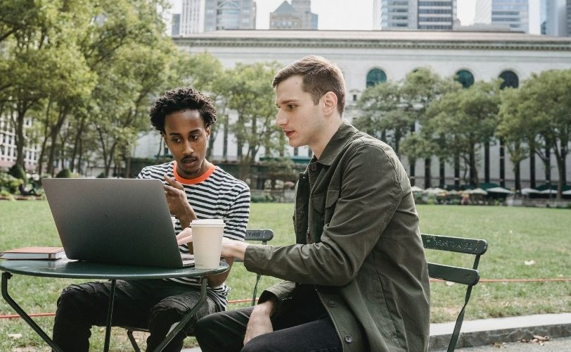 two men chatting and looking at laptop