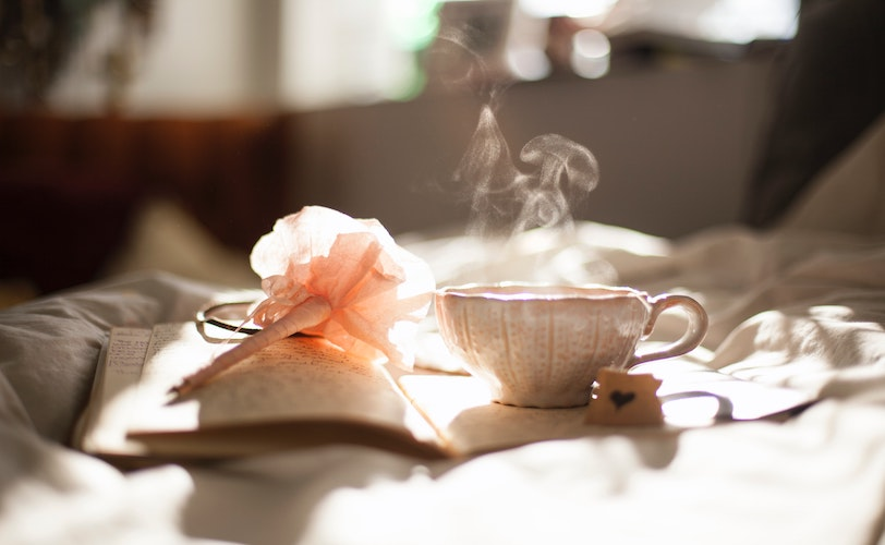 Cup of peppermint tea on bed with book