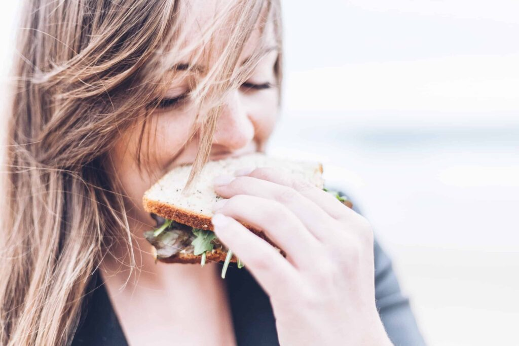 A woman eats a healthy sandwich