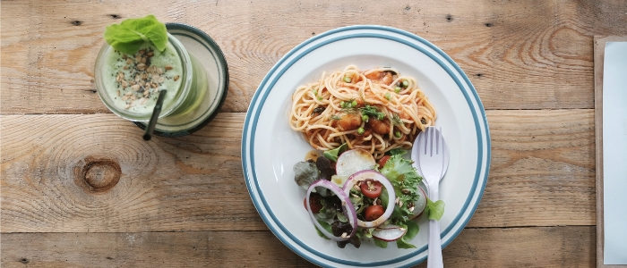 Plate of pasta and salad next to green smoothie