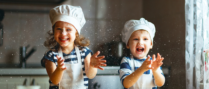 Young girl and boy preparing food and laughing