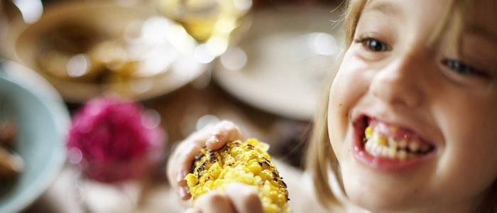 Child trying corn on the cob