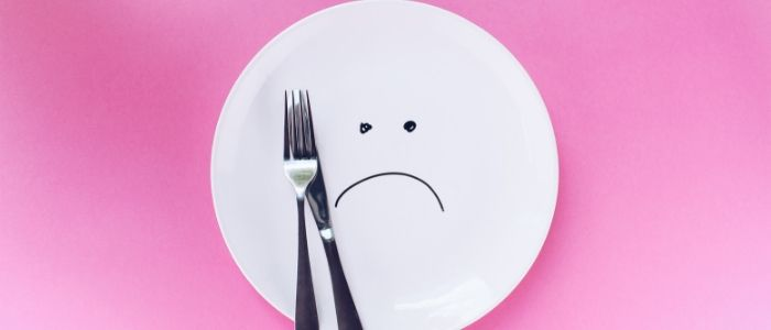 An empty plate with a sad smilie face drawn on it