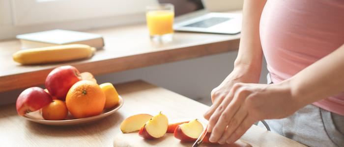 Mulher grávida, cortando uma maçã