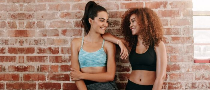 Two women smile together as they prepare to start in the gym