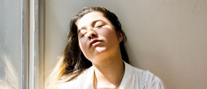 Woman with closed eyes in the sunshine