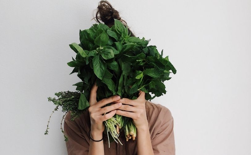 Woman holding veg in front of face