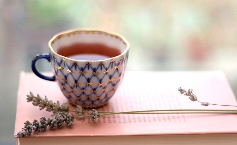 Cup of lavender tea on book