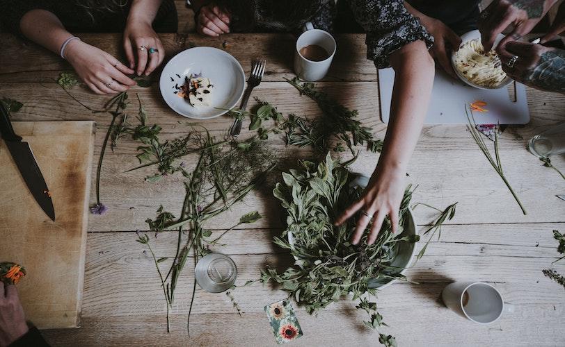 Three women mixing herbs