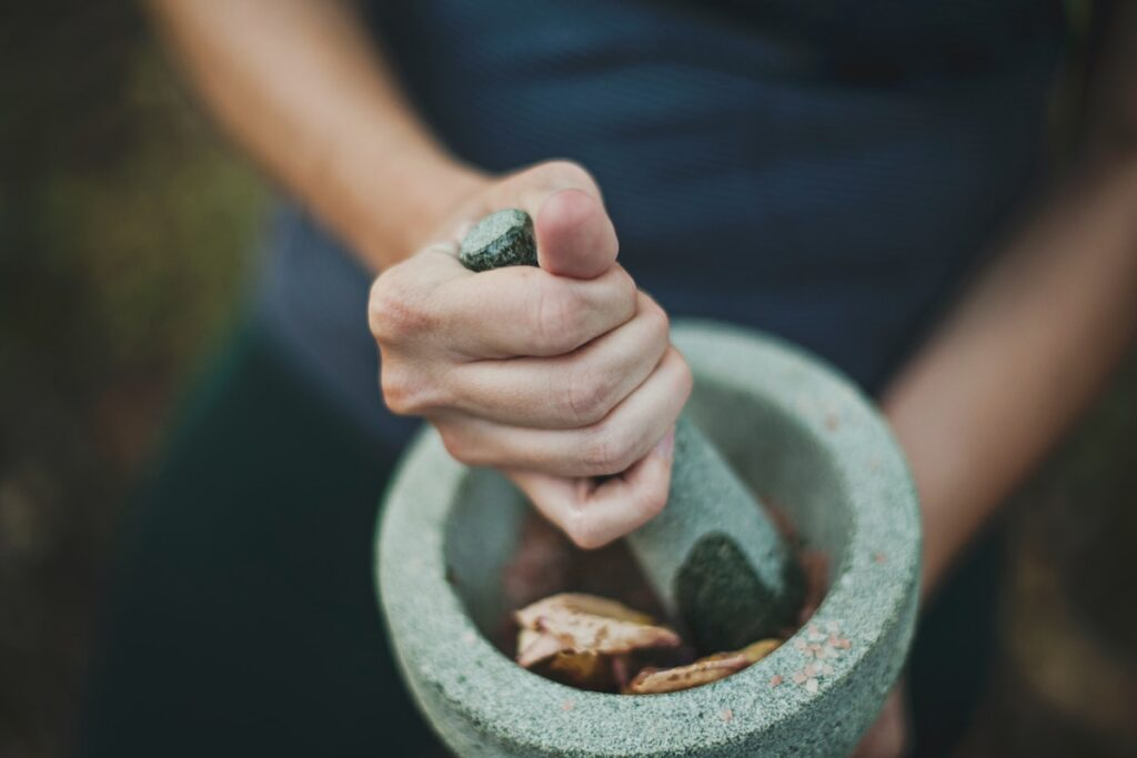 Woman preparing meal with pestle and mortar