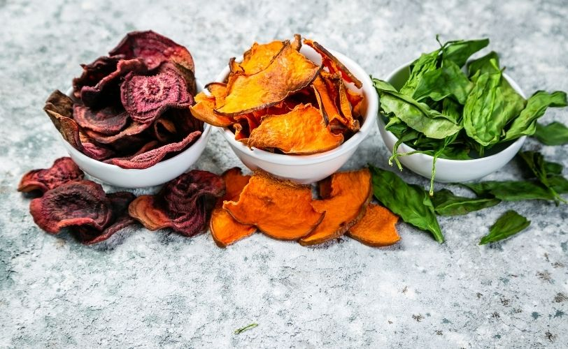 Three bowls of carrot, spinach and beetroot crisps
