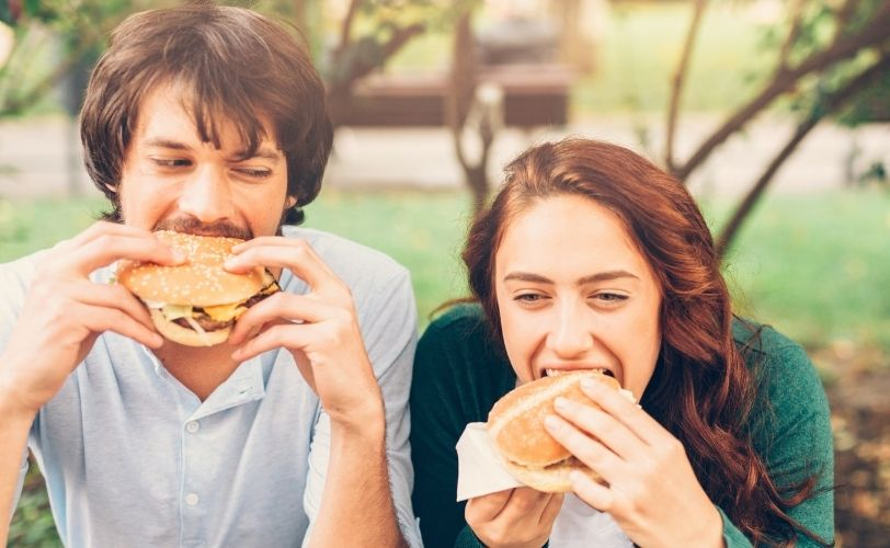 Couple eating burgers in park