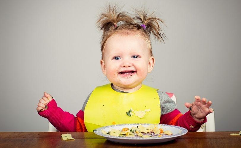 愉快的婴孩在餐桌上