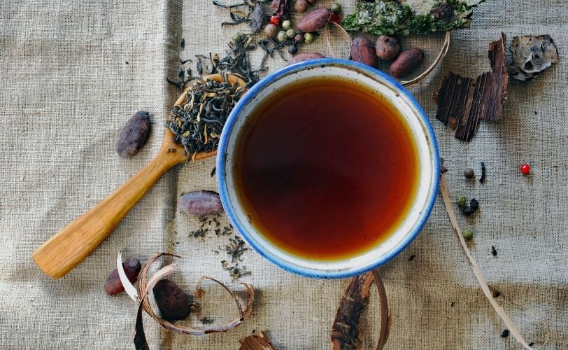 Tea cup surrounded by tea leaves