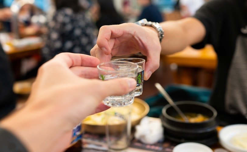 Two people touching shot glasses together