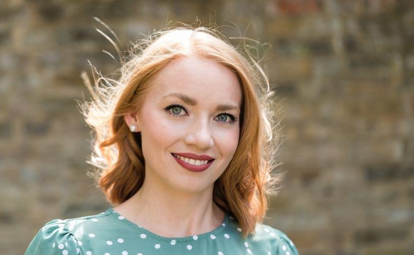 Photo of Emily John in polka dot top looking at camera