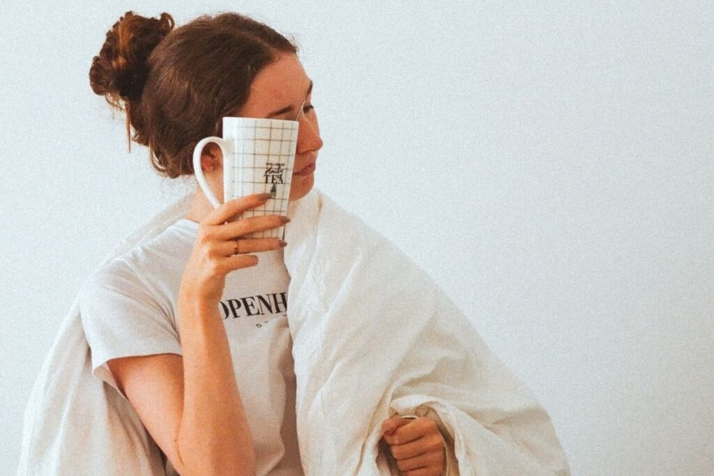Woman in duvet holding cup
