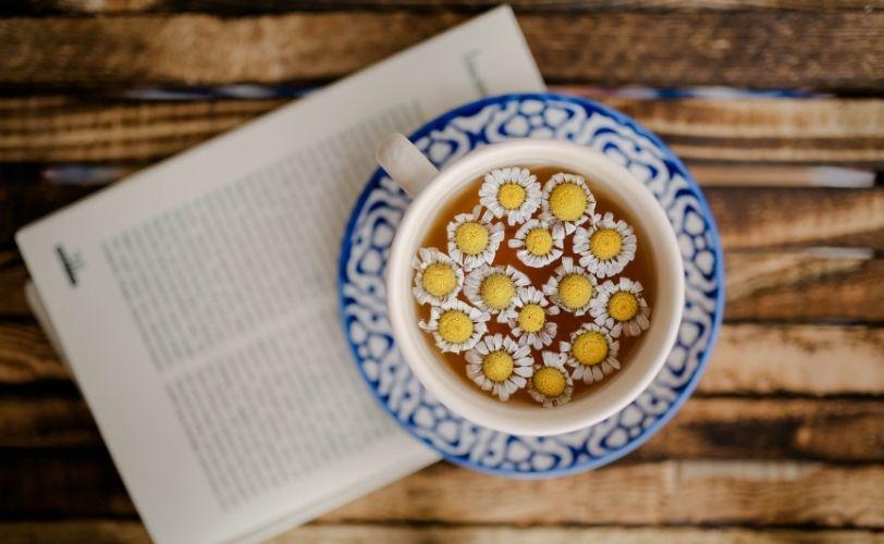 A cup of daisy tea on a book