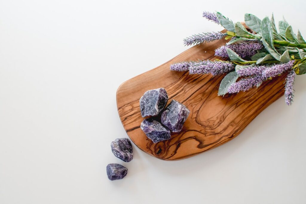 A chopping board with lavender and crystals