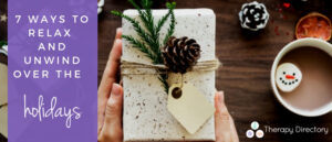 a hand holds a wrapped gift with a minecone decoration, a cup of hot chocolate to one side