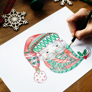 a hand colours a delicate santa pattern with colouring pencils