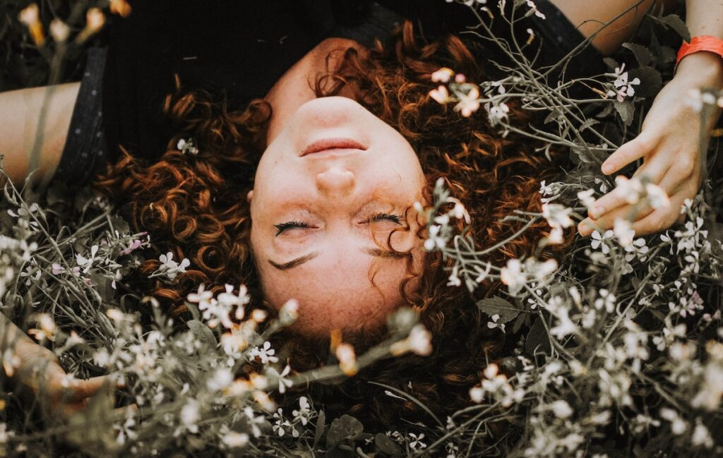 Woman laying in a field of white flowers