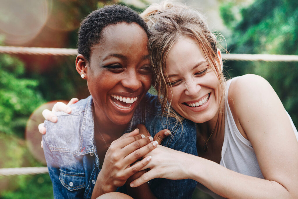 Image of two friends hugging and laughing together