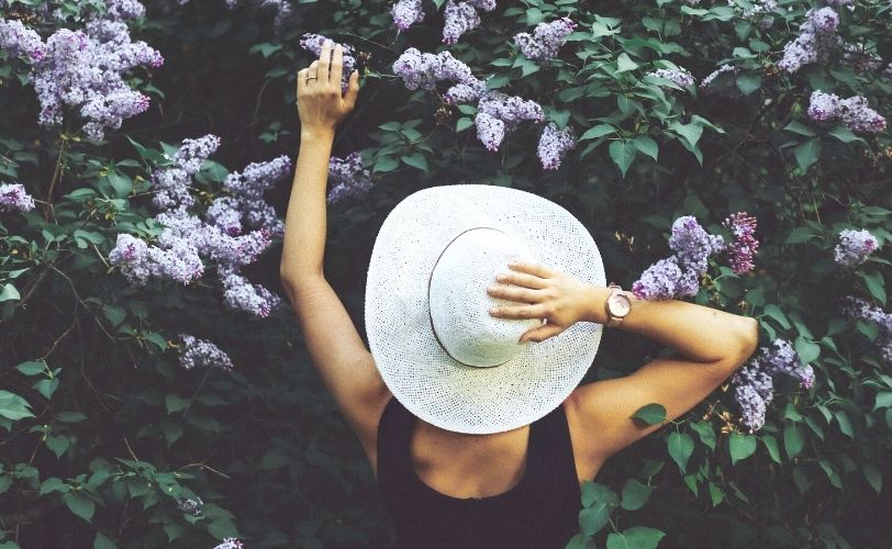 Woman holding hat looking at purple flowers