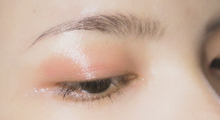 close up of woman's eye and eyebrow with glossy lid