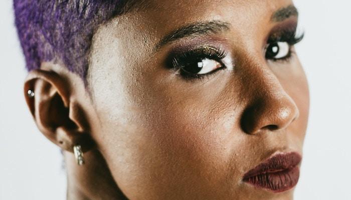 Purple haired woman wearing bold lip and smokey eye
