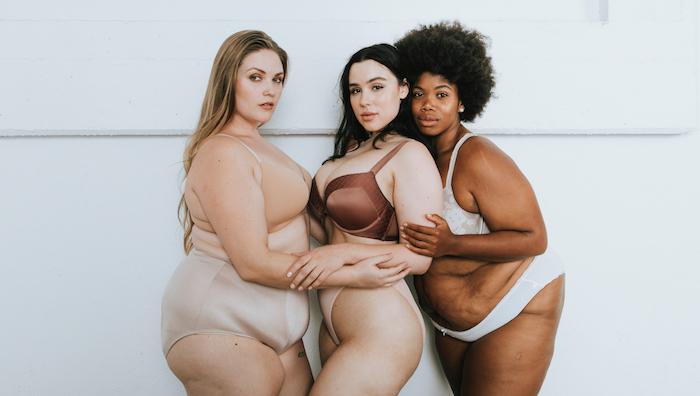 Three women in their underwear on white background