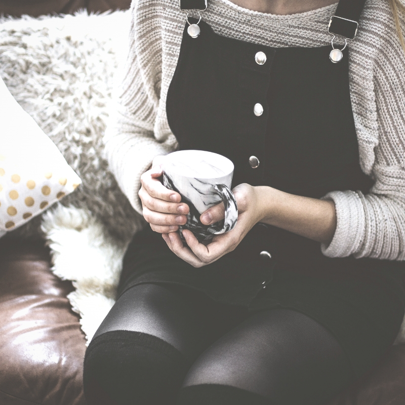 A woman sits on a couch with a cup of tea, talking to a therapist