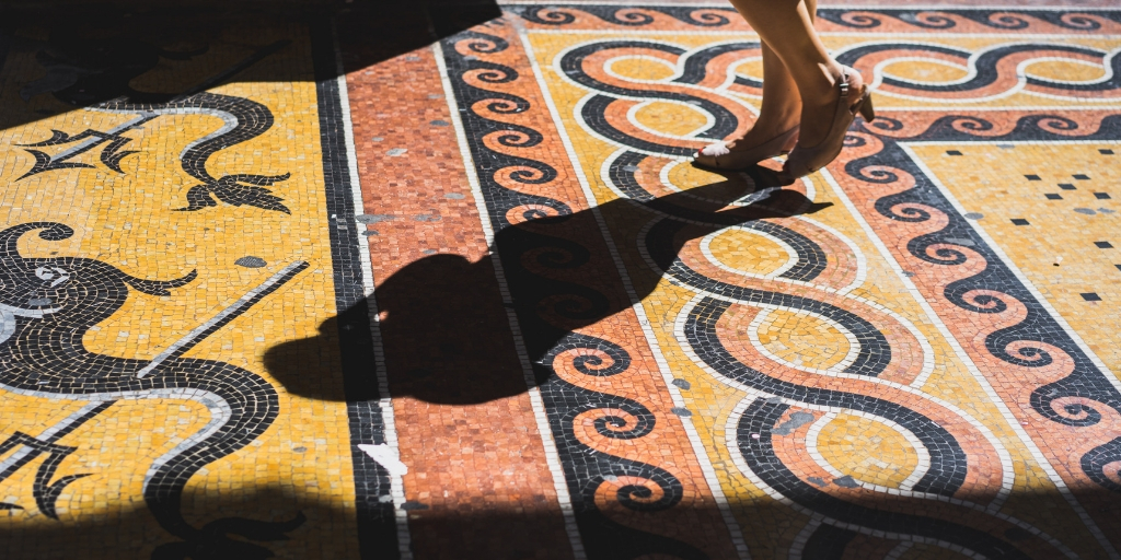 Close-up of a woman walking across an old mosaic floor